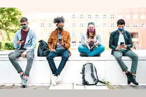 four students sitting on campus wall in front of brick building. all are wearing masks and looking at their phones. backpacks sitting nearby