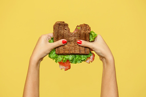 hands holding BLT with bite taken out