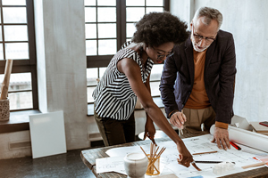 young black woman and older white man looking at paperwork in office