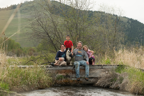 family of four: man, woman, two children under 10, with dog, pose on a rustic wooden bridge over a creek, mountain the background