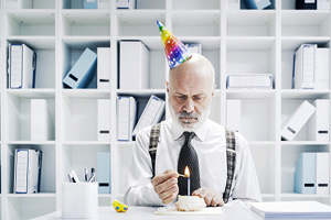 sad man at desk with party hat on lighting candle on cupcake