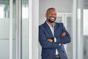 Smiling black man in navy suit leaning against doorway with arms crossed