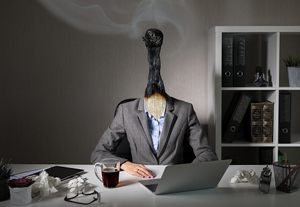 businessperson sitting at desk with burned matchtop for a head
