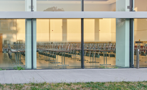 photo of large empty classroom with chairs upside down on rows of desks