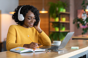 smiling black student with headphones and laptop, writing in textbook
