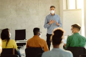 professor in mask teaches seated students in masks in college classroom
