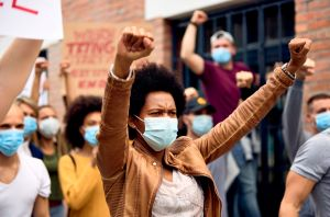 African American woman wearing protective face mask while protesting with arms raised.