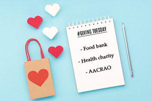 "on a blue table covered with red and white hearts, a notepad reads ""giving tuesday"" with a list below: food bank, health charity, aacrao"