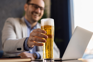 man in business suit at computer with pilsner