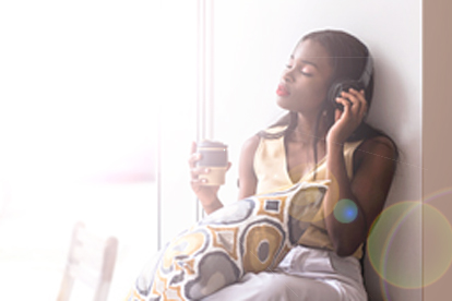 woman sitting near window with headphones on and drinking tea