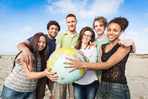 diverse group of students holding a globe together