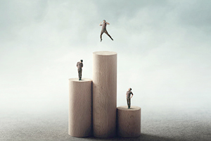 three pillars with people standing on them. the person on the highest podium is jumping with excitement
