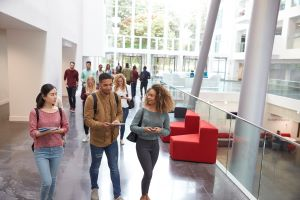 college students walk and talk with mobile devices in university building