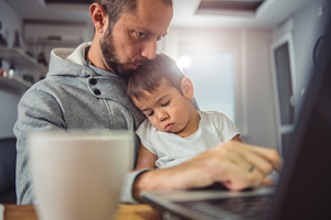 man sitting at laptop with child on lap