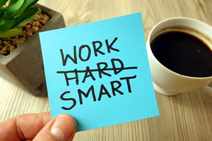 "hand holding post-it note reading ""work smart"" with the word ""hard"" crossed out above a table holding a cup of coffee and a cactus"