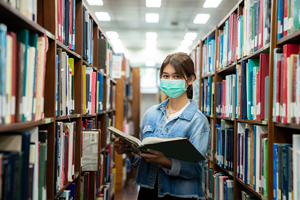 masked student in library holding book