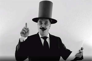 B&W photo of Steve Smith in top hat & fake mustache holding paper and pointing