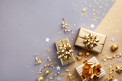three shiny golden gifts with golden bows against a silver and gold sparkling background with gold ornaments, ribbons, and silver stars sprinkled around